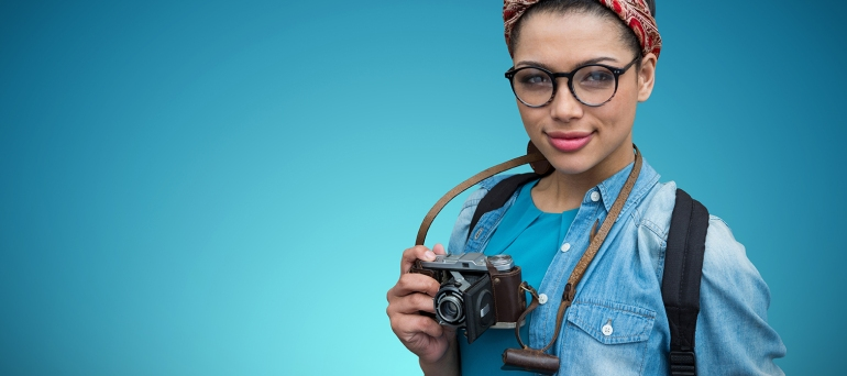 Composite image of portrait of female photographer with camera